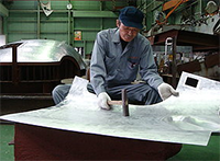 A hammer-wielding craftsman at Yamashita Kogyosho Co. is fashioning a nose for the latest-model Japanese bullet train, the E-6 series, scheduled to go into service in 2013.