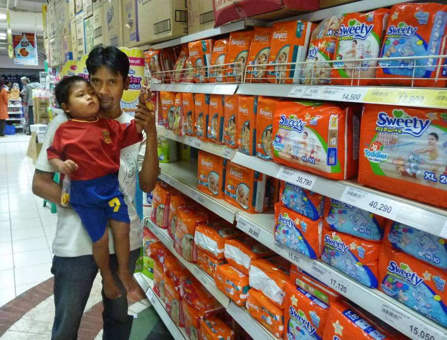 Growth market: A father and his son look for disposable paper diapers at a supermarket in Jakarta. Japanese diaper makers are banking on growing demand for their products in other Asian economies.