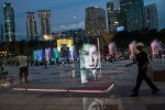 A Shiseido advertisement is reflected in a window in KLCC park outside the Petronas Twin Towers in Kuala Lumpur, Malaysia. (Sanjit Das/Bloomberg)